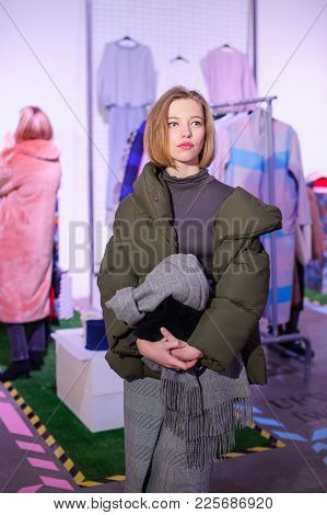 Fashionable Woman Posing Against  The Exhibition Visitors At A Fashion Show, Showing