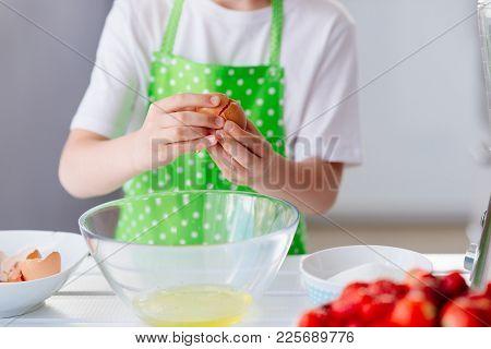 Child Boy Cracking Egg And Separating The Yolk
