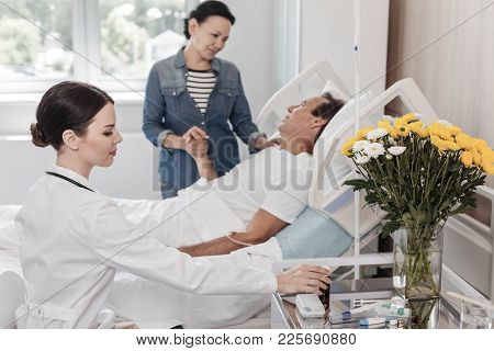 Loving Family. Selective Focus On A Female Doctor Taking A Bottle With Pillows While A Thoughtful Wo