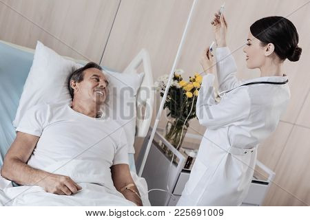 Thinking Positive Thoughts Only. Positive Minded Man Smiling While Looking At A Friendly Medical Wor