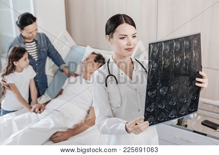 Good Results. Selective Focus On A Smiling Female Doctor Analyzing A Computed Tomography Scan Of A M