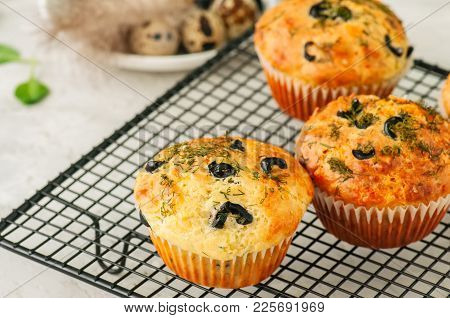 Savory Muffins With Olives And Herbs On A Wire Rack On A White Stone Backdrop. Rustic Style.