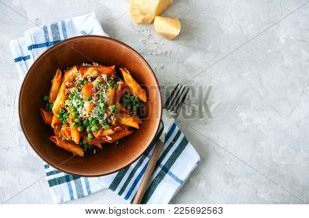 Tomato Sauce And Green Peas Penne Pasta In A Plate On A White Stone Background