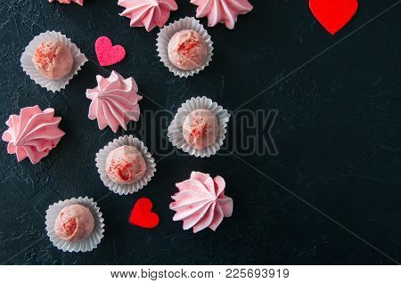 White Chocolate Strawberry Truffles And Pink Meringue Kisses On Black Stone Background