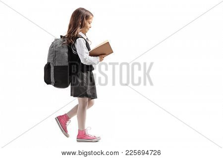Full length profile shot of a little schoolgirl walking and reading a book isolated on white background