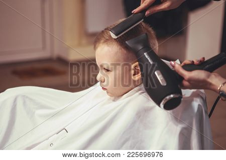 Little Boy At The Hairdresser. Child Is Scared Of Haircuts. Hairdresser's Hands Making Hairstyle To