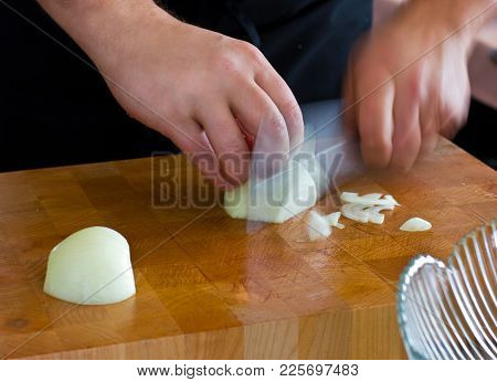 Men's Hands Shred White Onion On A Wooden Cutting Board