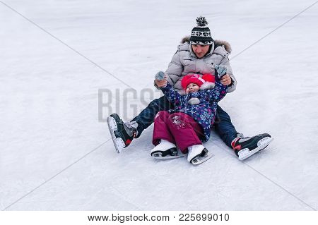 Little Adorable Girl Learning To Skate. Training In Skating. A Little Girl And A Young Man Fell On T