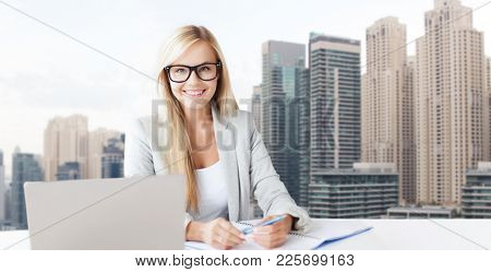 business and people concept - smiling businesswoman with notepad and laptop at office over dubai city skyscrapers background