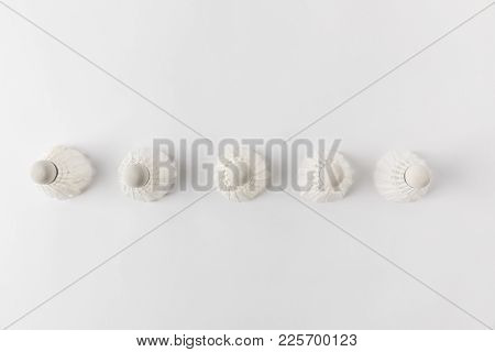 Top View Of Badminton Shuttlecocks In Row On White Surface