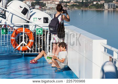 Corsica, France - July 2, 2015: Young Mother Takes Photo On A Smartphone From Passenger Ferry Deck,