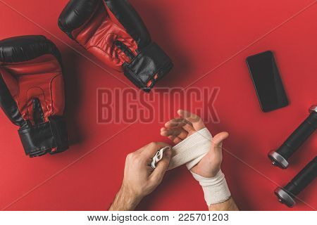 Cropped Shot Of Boxer Covering Up Hands In Elastic Bandage On Red Surface