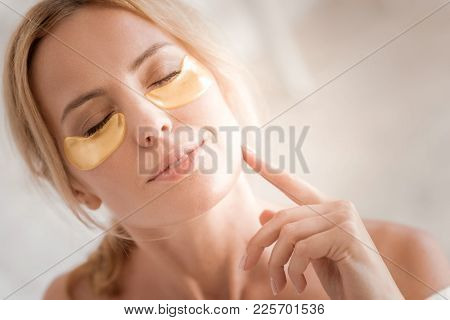 Fresh Look. Nice Relaxed Attractive Woman Smiling And Closing Her Eyes While Using Eye Patches