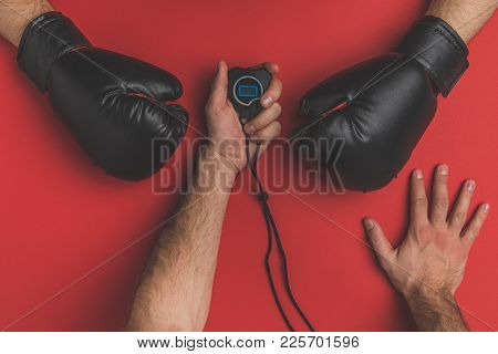 Cropped Shot Of Fighter In Gloves And His Trainer With Stopwatch On Red Tabletop