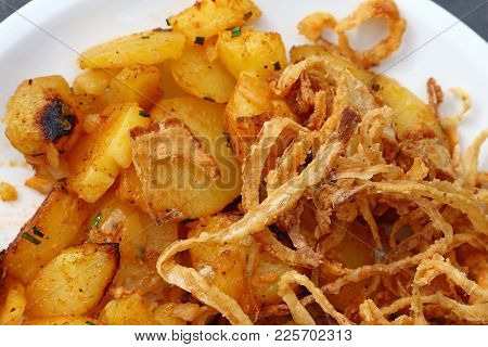 Close Up Portion Of Roasted Potato And Fried Onion Rings On White Plate Over Grey Table, Elevated To