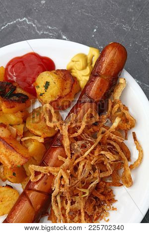 Close Up Portion Of One Big Grilled Sausage With Homemade Roasted Potato, Fried Onion Rings, Ketchup
