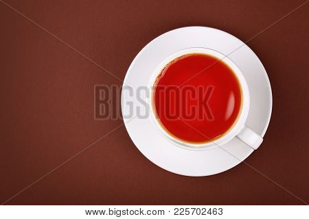 Close Up White Cup Full Of Red Black Tea On Porcelain Saucer Over Brown Paper Background, Close Up,
