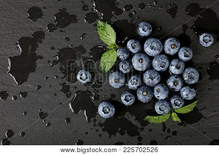 Close Up Fresh Washed Blueberry Berries With Water Drops And Green Mint Leaves On Black Slate Board,