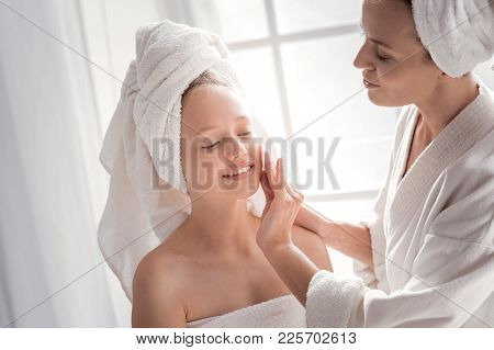 Face Cleansing. Positive Nice Pleasant Woman Holding A Cotton Pad And Cleaning The Face Of Her Daugh
