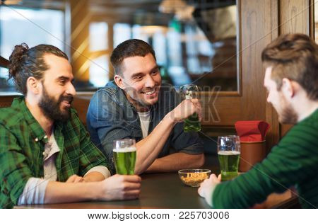 people, leisure and st patricks day concept - happy male friends drinking green beer at bar or pub