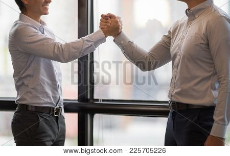 Business Partners Giving Fist Bump After Complete A Deal On Cityscape Background. Successful Teamwor