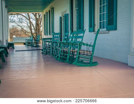 Green Wooden Rocking Chairs On A Porch In The Usa
