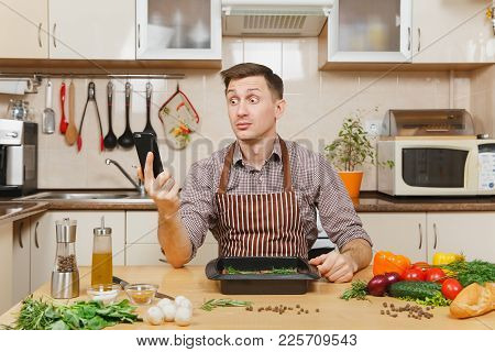 Perturbed Stress Young Man In Apron Sitting At Table With Vegetables, Talking On Mobile Phone, Cooki