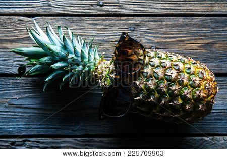 Ripe Pineapple With Sunglasses On A White Wooden Table. Fruit, Nature, Food A