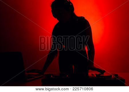 Silhouette Of A Dj Girl At A Party Behind A Music Console
