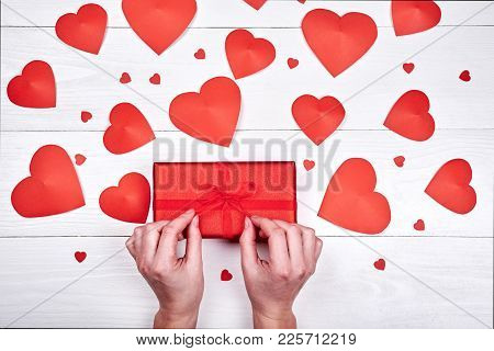 Woman Holding And Unwrapping Red Gift Box On Table With Red Hearts. Greeting Card For Valentins Day,