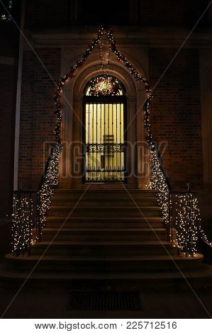 Front Door Steps And Metal Gate Door With Banisters Adorned With Lights For Christmas Holiday Season