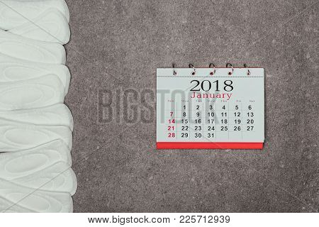 Top View Of Arranged Menstrual Pads And Calendar On Grey Surface