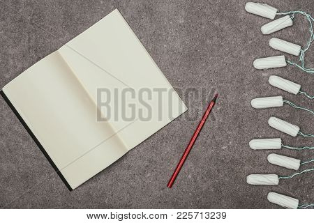Top View Of Empty Notebook, Marker And Menstrual Tampons On Grey Surface