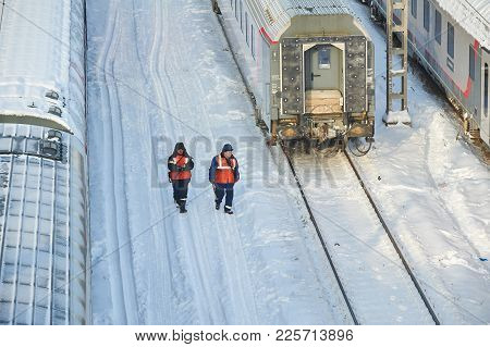 Moscow, Feb. 01, 2018: Winter Day View On Railway Maintenance Workers In Orange High-visibility Vest