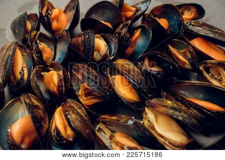 Fresh Uncooked Raw Big Mussels On Chipped Ice On Black Iron Plate Over Dark Slate Stone Background,
