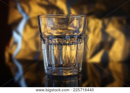 Faceted Glass Half Filled With Water, Gold Background