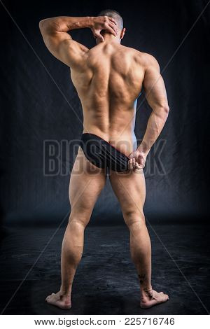 Muscular Man Pulling Down Underwear To Show His Butt, In Studio Shot