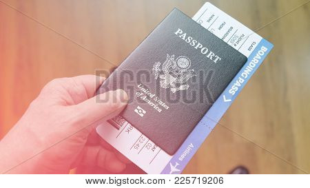 Persons Hand Holding And Giving Passport Of United States And Boarding Pass