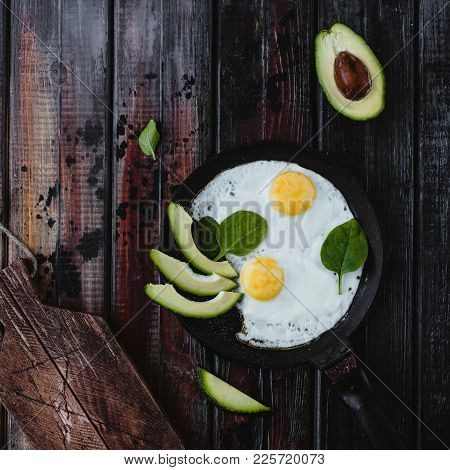 Top View Of Fried Eggs With Spinach And Pieces Of Avocado On Wooden Tabletop