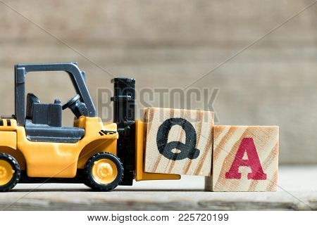 Toy Yellow Forklift Hold Letter Block Q To Complete Word Qa (abbreviation Of Quality Assurance Or Fr