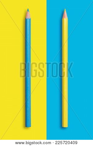 Two Pencils Of Yellow And Blue On A Blue And Yellow Background, Symbolize The Opposite