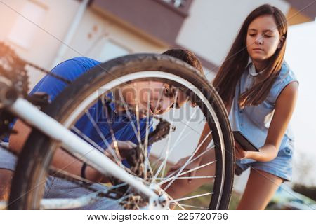 Teenager Boy Repair Tire On Bicycle , Female Friend Sitting Next To Him, Using Digital Tablet For In