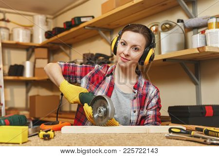 Young Brown-hair Woman In Plaid Shirt, Gray T-shirt, Noise Insulated Headphones, Yellow Gloves Worki