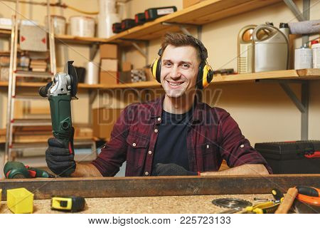 Handsome Smiling Caucasian Young Man In Plaid Shirt, Black T-shirt, Noise Insulated Headphones Worki