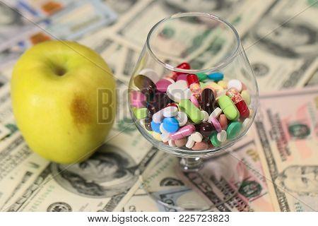 fresh apple and medicine on paper denominations dollars