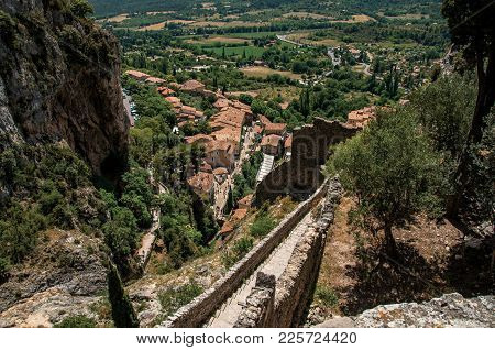View Of Stone Staircase, Roofs And Belfry Under Sunny Blue Sky In The Charming Village Of Moustiers-