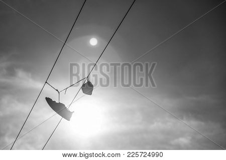 Sneakers Hang On Electric Line Wire Cable With Sun And Sky On Background. Funny Urban Outdoor Footwe