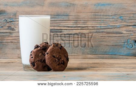 Chocolate chip cookies, glass cup milk on rustic wood background