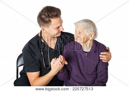 Senior Ill Woman With Friendly Male Carer On Isolated Background