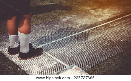 Students Boy Taking Long Jump On Rubber Board During A School Sport Competition Day. School Sports D